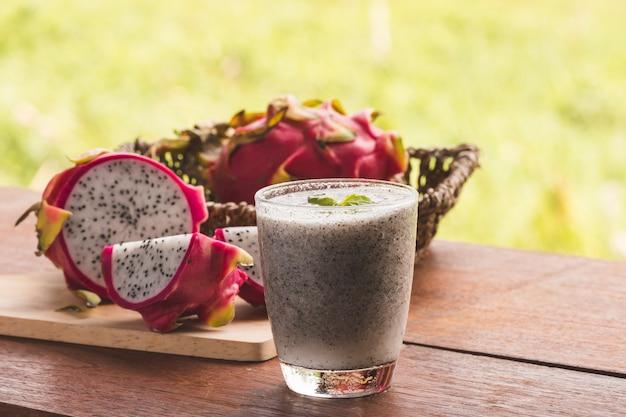 Ein glas drachenfrucht smoothie und frische drachefrucht auf holztisch
