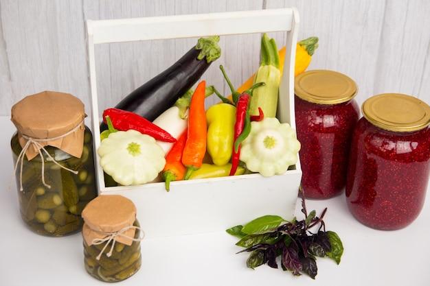Ein glas eingelegte gurken und eine frisch geerntete gemüseernte. paprika aubergine und tomaten