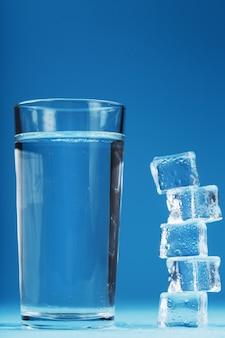 Ein glas eis und klares wasser, eiswürfel auf blauem grund. ein erfrischendes getränk an heißen tagen. freiraum