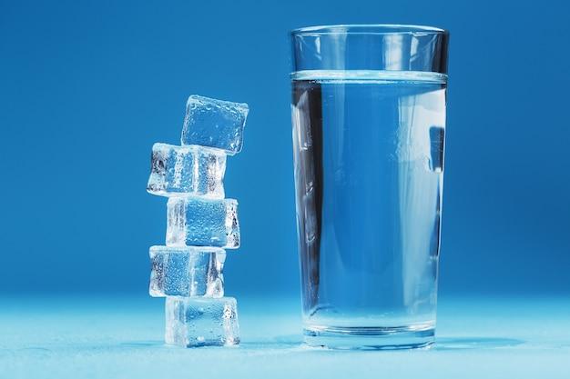 Ein glas eis und klares wasser, eiswürfel auf blauem grund.