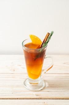 Ein glas eisgekühlter americano-schwarzkaffee und eine schicht orangen- und zitronensaft, dekoriert mit rosmarin und zimt auf holztisch