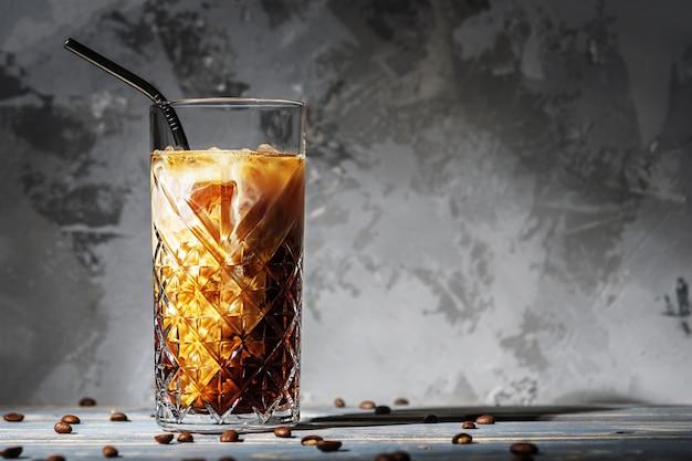 Ein glas eiskaffee mit milch gegen eine betonwand mit kopien des raumes.