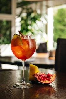 Ein glas eiskalter aperol-spritz-cocktail, serviert in einem weinglas mit ananas und granat, auf einen tisch im restaurant gestellt