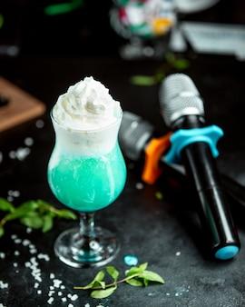 Ein glas exotischer cocktail, garniert mit schlagsahne im karaoke-club