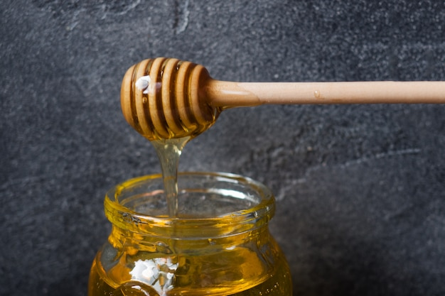 Ein glas flüssiger honig aus lindenblüten und ein stab mit honig auf dunkler oberfläche.