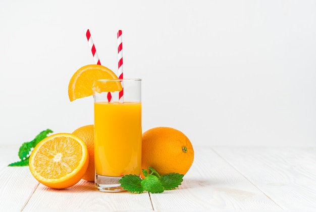 Ein glas frisch gepresster orangensaft mit einer orangenscheibe und tuben auf einem hellen schreibtisch mit orangen und minze.