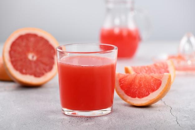 Ein glas frisch zubereiteter grapefruitsaft und frische obstscheiben auf hellem betonhintergrund. gesundes und diätgetränk. nahaufnahme