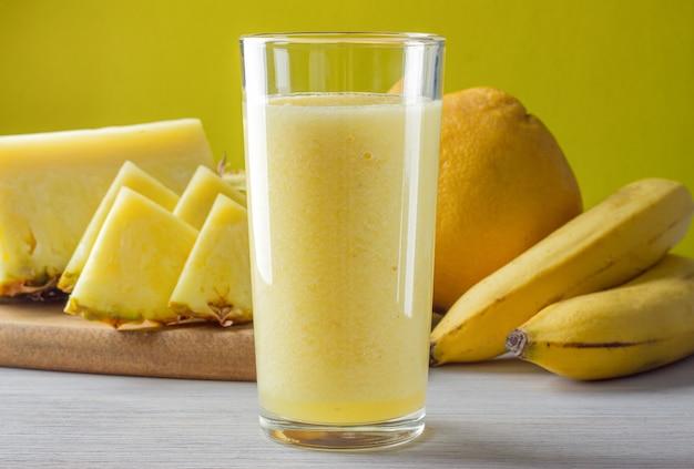 Ein glas frische banane, ananas, orange smoothie auf weißem tisch