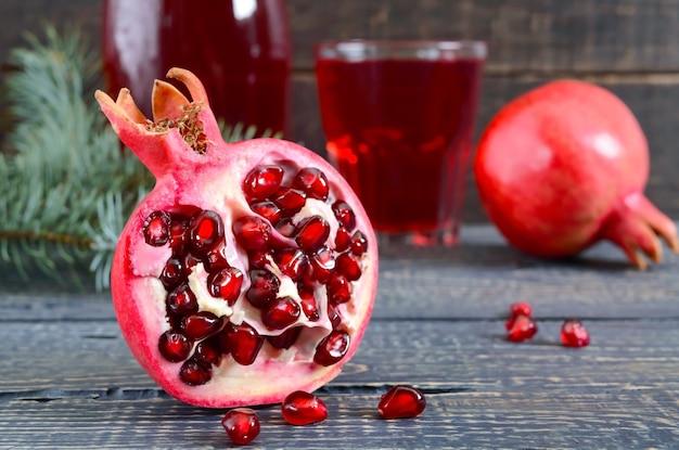 Ein glas frischer granatapfelsaft mit reifen granatapfelfrüchten auf holztisch. vitamine und mineralien. gesundes getränkekonzept. nahaufnahme