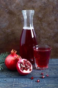 Ein glas frischer granatapfelsaft mit reifen granatapfelfrüchten auf holztisch. vitamine und mineralien. gesundes getränkekonzept. vertikale ansicht