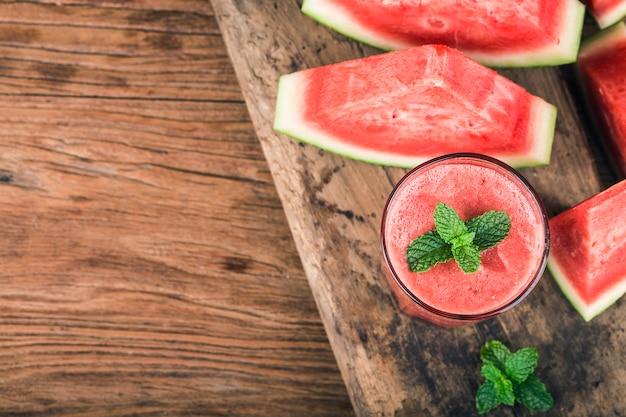 Ein glas frischer wassermelonensaft auf einem hintergrund des hölzernen brettes