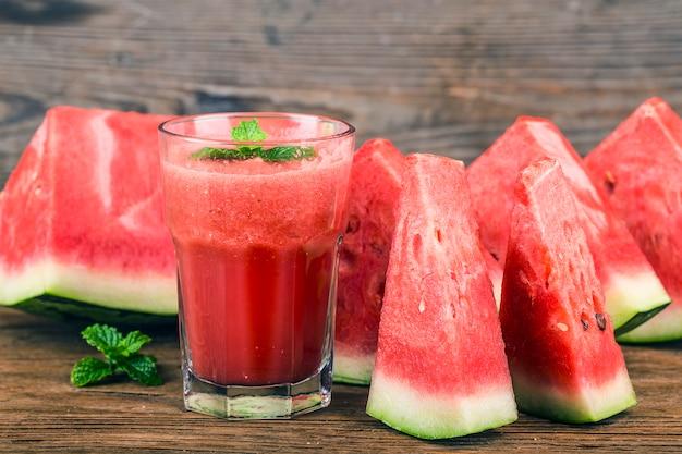 Ein glas frischer wassermelonensaft auf einem hölzernen brett