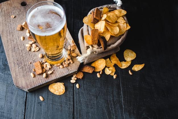 Ein glas frisches bier mit kartoffelchips und erdnüssen auf schwarzem hintergrund