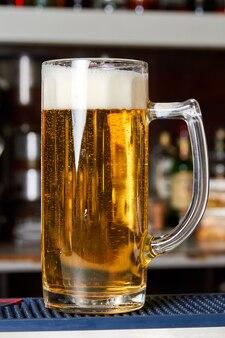 Ein glas frisches schaumiges bier auf der theke