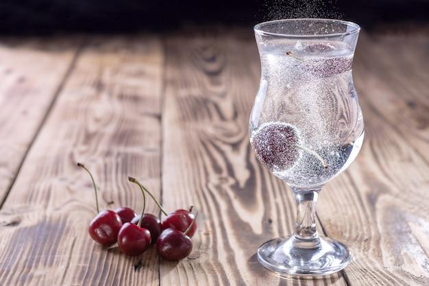 Ein glas frisches sprudelwasser mit einer kirsche auf holzhintergrund