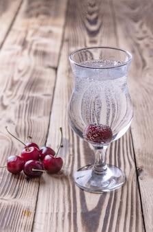 Ein glas frisches sprudelwasser mit einer kirsche