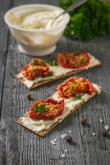 Ein glas frischkäse und toast mit sonnengetrockneten tomaten auf einem holztisch. vegetarischer snack aus hüttenkäse und tomaten.