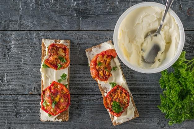 Ein glas frischkäse und toast mit sonnengetrockneten tomaten auf einem holztisch.