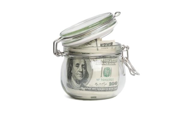 Ein glas gefüllt mit dollar unter hundert dollarscheinen.