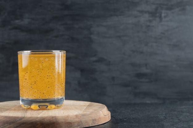 Ein glas gelber orangensaft auf schwarz auf einem stück holzbrett