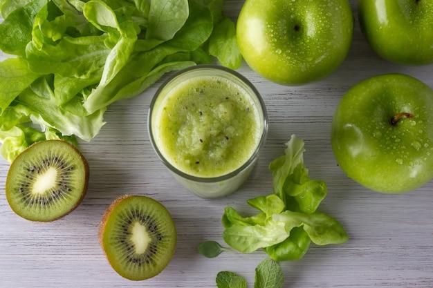 Ein glas gesunder grüner smoothie mit apfel, kiwi und blättern auf dem weißen holztisch