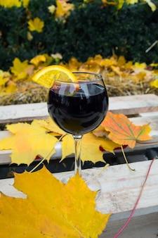 Ein glas glühwein in einem kalten herbst, vor dem hintergrund der gelben und roten blätter