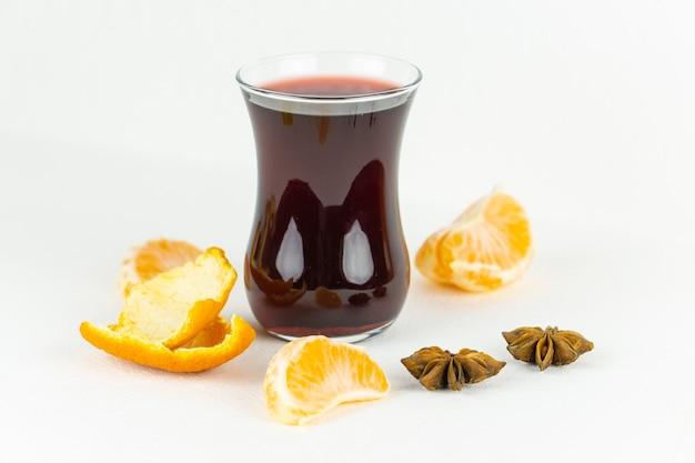 Ein glas glühwein mit mandarinenschale und anissamen