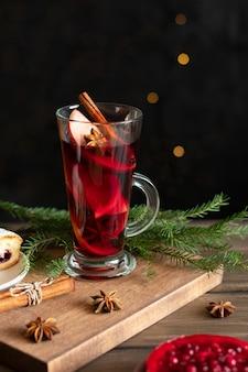 Ein glas glühwein zu weihnachten mit gewürzen und beerenkuchen