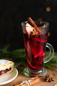 Ein glas glühwein zu weihnachten mit gewürzen und einem beerenkuchen Premium Fotos