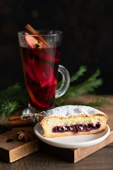Ein glas glühwein zu weihnachten mit gewürzen und einem beerenkuchen