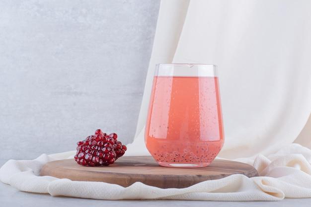 Ein glas granatapfelsaft auf holzbrett mit samen. foto in hoher qualität