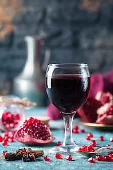 Ein glas granatapfelsaft mit frischen granatapfelfrüchten und tannenzweigen auf blauem tisch. gesundes getränkekonzept.