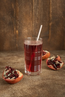 Ein glas granatapfelsaft und rote granatapfelfruchtstücke auf braunem holzhintergrund, vertikal