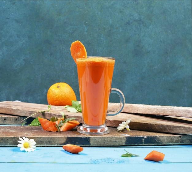 Ein glas grapefruit-smoothie auf einem stück holz.
