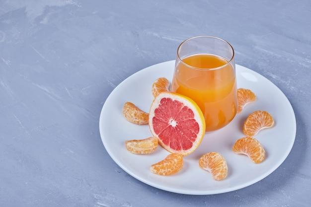 Ein glas grapefruitcocktail mit obstsalat.
