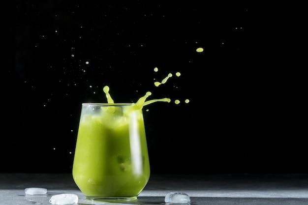 Ein glas grüner cocktail mit eis und spritzer auf einem dunklen hintergrund.