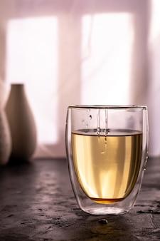 Ein glas grüner tee mit honig auf einem tisch