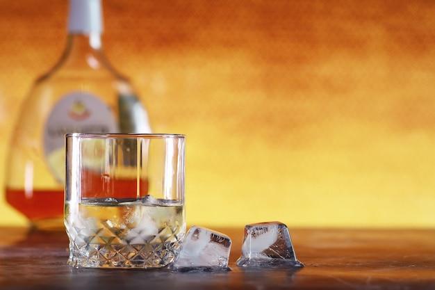 Ein glas harter alkohol mit eis auf einer bartheke. whisky mit soda in einem glas. werbung für alkoholisches getränk.
