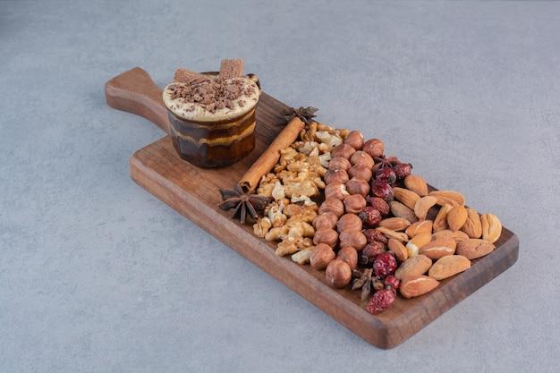 Ein glas heiße schokolade mit verschiedenen nüssen auf holzbrett.