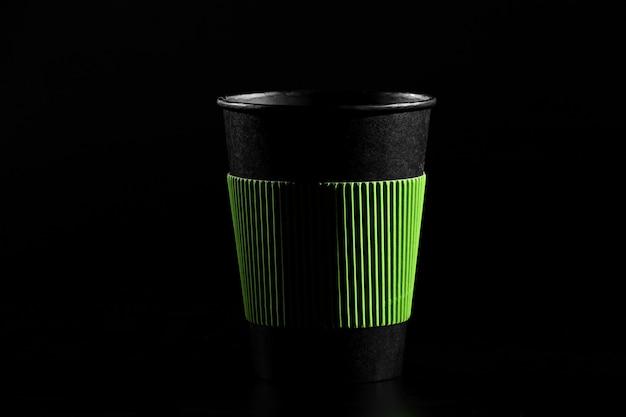 Ein glas heißen tee oder kaffee. schwarzes papierglas mit einem deckel auf einem schwarzen hintergrund.