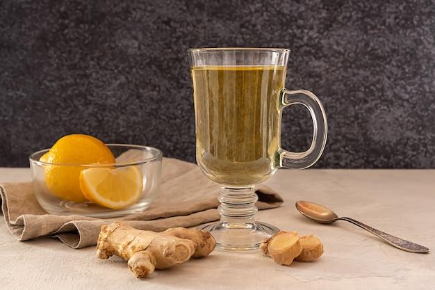 Ein glas heißer ingwer-zitronen-tee mit zitronen- und ingwerwurzelscheiben auf holztisch