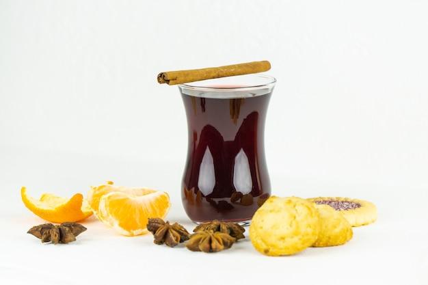 Ein glas heißer rotwein mit zimt-anis und süßen keksen
