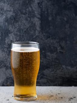 Ein glas helles bier auf einem dunklen hintergrund