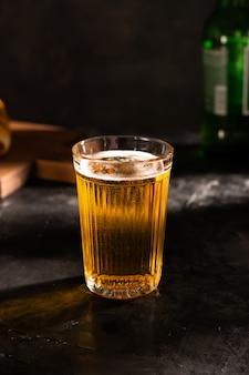 Ein glas helles bier mit schaum auf einem schwarzen tisch