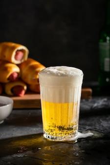 Ein glas helles bier mit schaum und würstchen im teig auf dem holzbrett