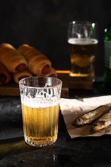 Ein glas helles bier und zwei getrocknete fische auf einem schwarzen tisch