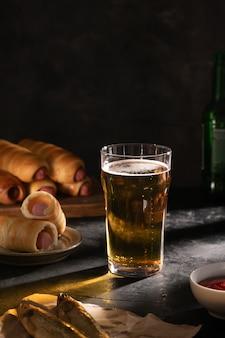 Ein glas helles bier, zwei getrocknete fische, würstchen im teig und sauce