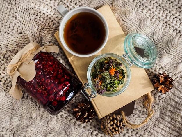 Ein glas himbeermarmelade, eine tasse tee und ein buch auf einer wolldecke. zapfen und trockene kräuter für tee. volksmedizin.