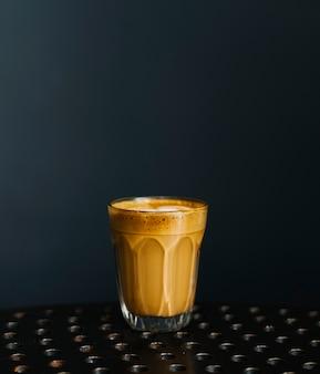 Ein glas kaffee auf einem tisch