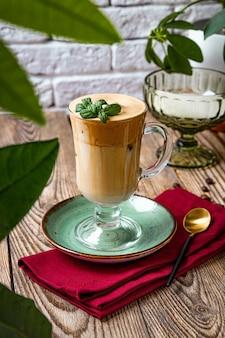 Ein glas kaffee mit milch verziert mit minzblättern auf dem tisch in einem café, dalalona-kaffee, vertikales foto.